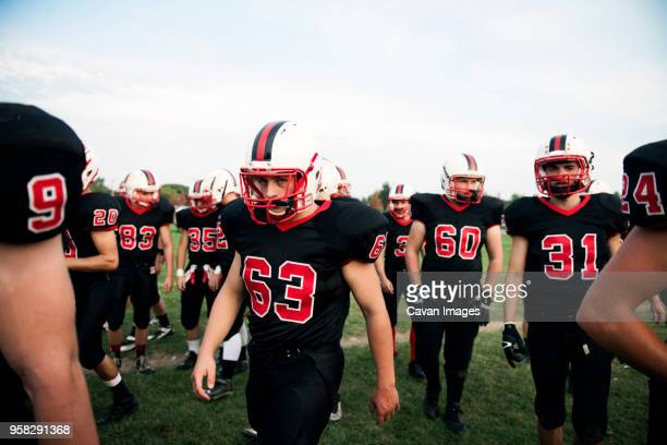 american football team walking on playing field against sky - high school football stock pictures, royalty-free photos & images