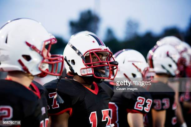 american football team with sports helmet on field - high school football stock pictures, royalty-free photos & images