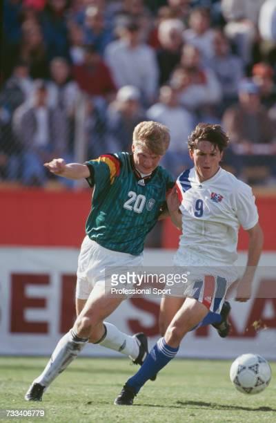 American footballer JoeMax Moore and German footballer Stefan Effenberg both run to win the ball during the international friendly match between...