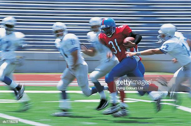 American Footballer Running Away From Defenders
