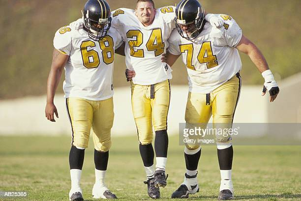 american footballers assisting injured team mate - american football sport stock photos and pictures
