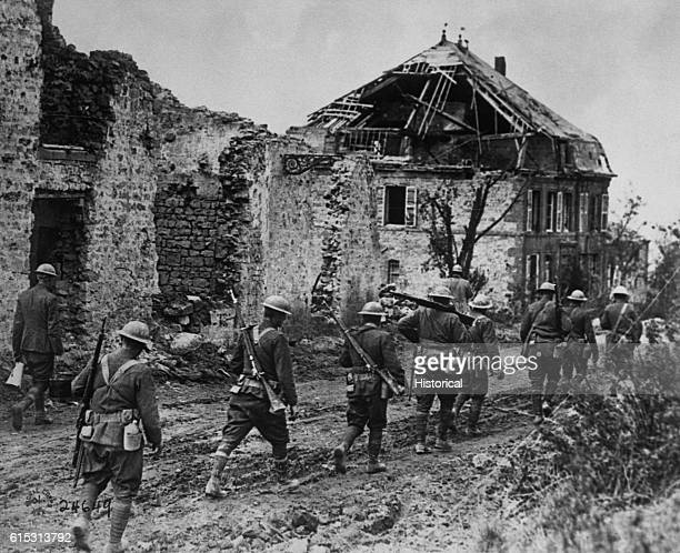 American forces march past the ruins of a house that had been used as an observatory by the enemy A periscope protrudes from the far end of the roof...