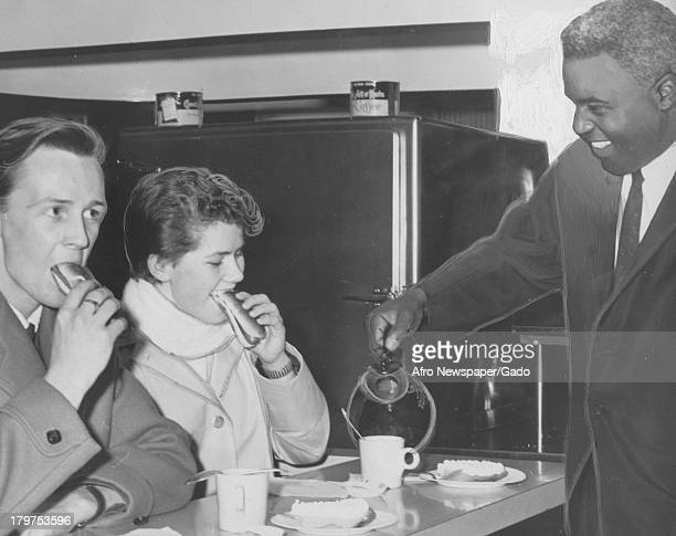American former baseball player Jackie Robinson of the Brooklyn Dodgers, vice president of Chock Full O' Nuts, greets Janet Adams and Bruce McMillen...