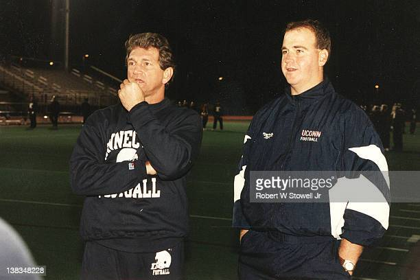 American former professional football player Joe Theisman stands with University of Connecticut football coach Skip Holtz during a night practice,...
