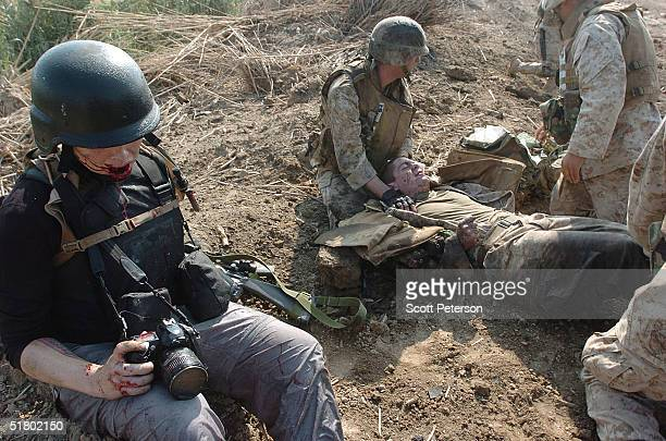 American freelance photographer Stephanie Kuykendal and Corporal Ian McHugh lie wounded after US Marines of the Light Armored Reconnaissance company...