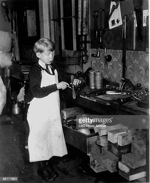 American future businessman and CBS president Frank Stanton stands dressed in an apron next to a workbench full of tools and tightens the screws of a...