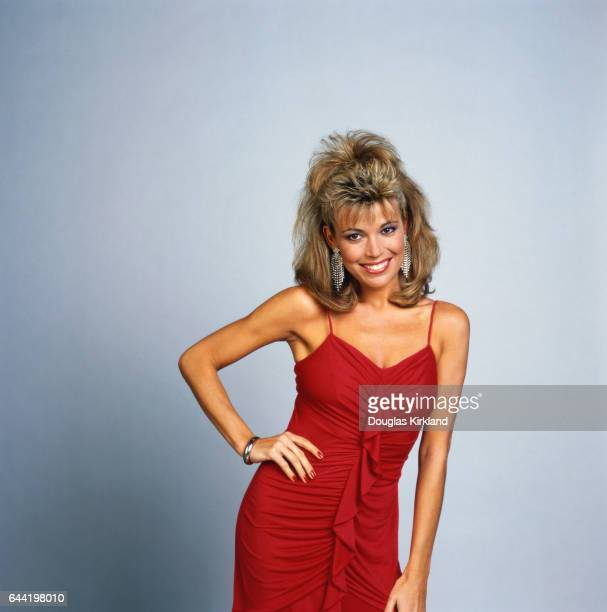 American game show assistant for Wheel of Fortune Vanna White poses in a red dress with her hand on her hip