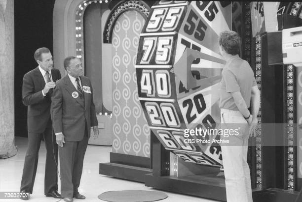 American game show host Bob Barker advises a contestant about spinning the big wheel as another contestant looks on during the 15th Anniversary...