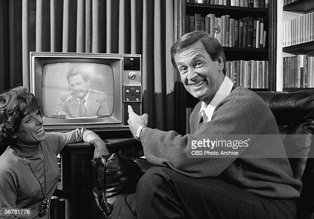 American game show host Bob Barker looks at the camera and smiles while he points to himself on a nearby television screen as his wife Dorothy Jo...