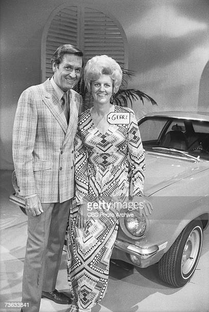 American game show host Bob Barker poses with an undientified contestant as they stand by a new car during an episode of the CBS game show 'The Price...