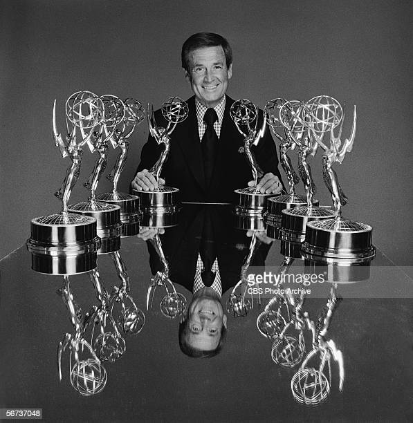 American game show host Bob Barker sits at a table with a group of Emmy statues to publicize the Daytime Emmy Awards March 17 1976