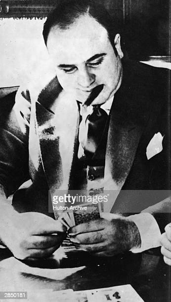 American gangster Al Capone plays cards in a train compartment during his transport to prison to serve a sentance for tax evasion, October 1931.