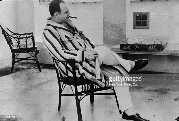 American gangster Al Capone relaxes in his vacation home, Miami, Florida, 1930. Capone smokes a cigar and wears a striped dressing gown and slippers.