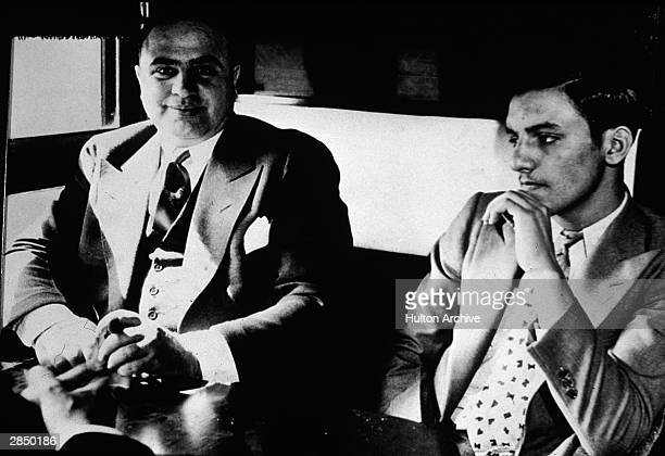 American gangster Al Capone sits in a train compartment with an unidentifed associate during his transport to prison to serve a sentance for tax...