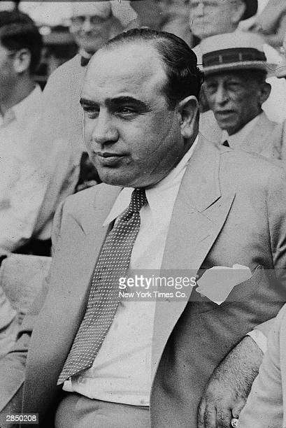 American gangster Al Capone wears a light colored suit and sits among a crowd, circa 1931.
