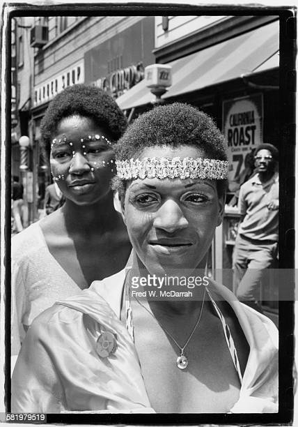 American gay liberation activist Marsha P Johnson wearing headband and an unidentified woman in facepaint on 7th Avenue South attend the second...
