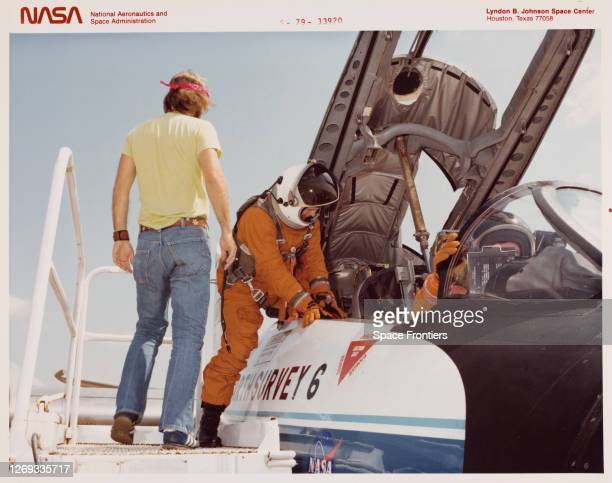 American geologist and NASA astronaut candidate Kathryn D Sullivan wearing an orange jumpsuit and crash helmet climbs into a NASA WB57F...