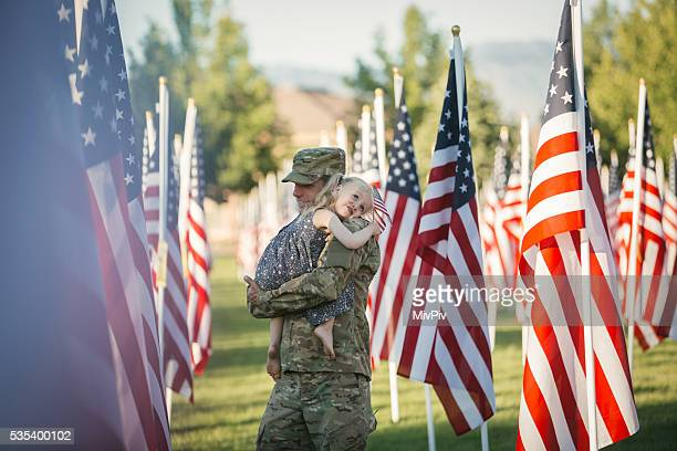 American girl hugging her dad in front of American flags