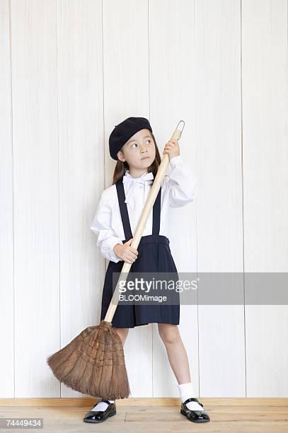american girl weaing uniform of school ,holding  broom - 箒 ストックフォトと画像