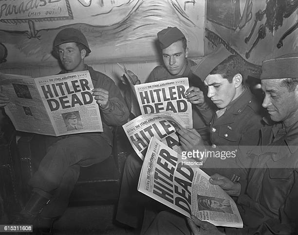American GIs on leave in Paris reading the US military newspaper Stars and Stripes which has a headline announcing Hitler's death The German dictator...