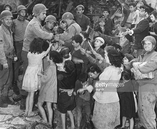 American GIs provide some Christmas cheer for the children of an Italian village demolished by the retreating German army, donating gifts from their...