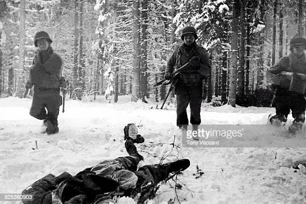 American GIs stand over the body of a dead German soldier, Battle of the Bulge, Ardennes, Belgium, World War II, December 1944.