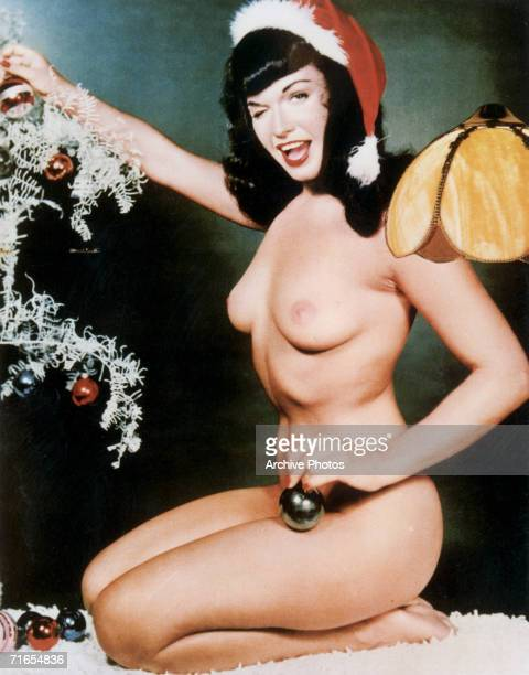 American glamour model and pinup girl Bettie Page poses in the nude with a Christmas bauble circa 1955