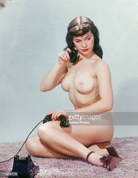American glamour model and pinup girl Bettie Page poses nude with an address book and a telephone circa 1955