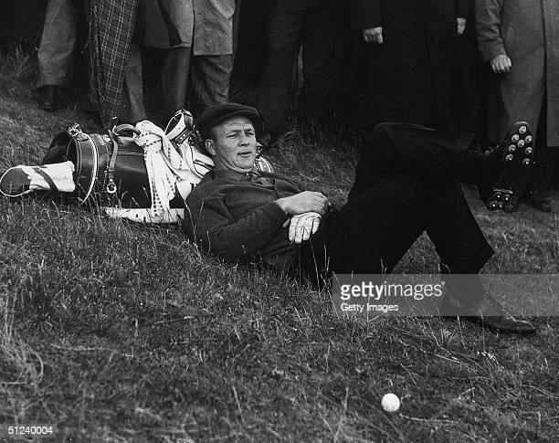 1961 American golfer Arnold Palmer lays his head on his golf bag while taking a break between shots during a golf tournament