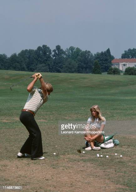 American golfer Ben Crenshaw takes some practice shots watched by his wife Polly circa 1976