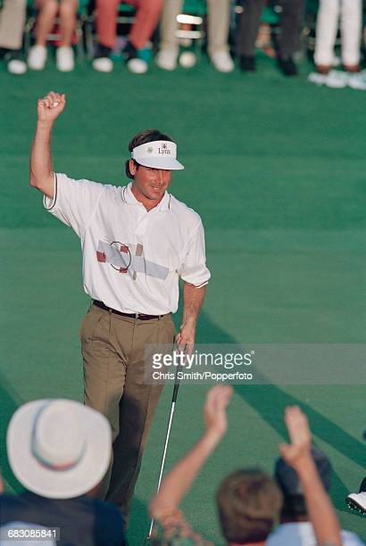 American golfer Fred Couples pictured raising his arm in the air on the 18th green during competition in the final round to finish in first place to...