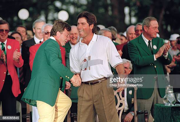 American golfer Fred Couples pictured right shaking hands with the previous year's winner Welsh golfer Ian Woosnam at the green jacket presentation...