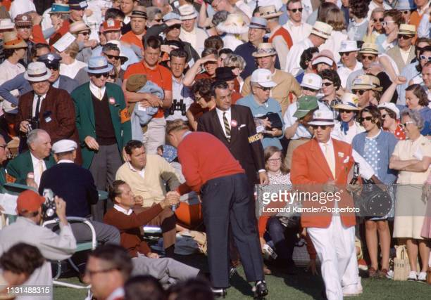 American golfer Jack Nicklaus shaking hands with Tommy Jacobs watched by Gay Brewer who would be his two playoff opponents after missing his putt on...