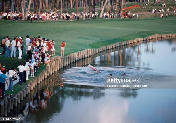 American golfer Jerry Pate dives into the water hazard after pushing in Tour Commissioneer Deane Beman and Golf Course Designer Pete Dye following...