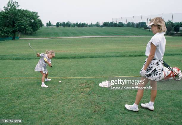 American golfer Laura Baugh during a practice session with her little daughter Chelsea circa 1986