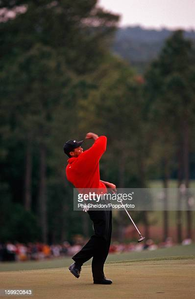 American golfer Tiger Woods celebrates after making his final putt on the 72nd hole to win his first major championship and the US Masters Golf...