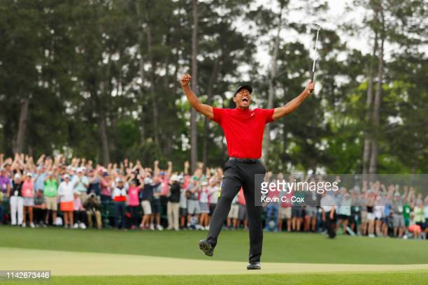 American golfer Tiger Woods celebrates after sinking his putt on the 18th green to win during the final round of the Masters at Augusta National Golf...