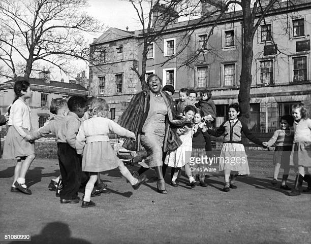 American gospel singer songwriter and electric guitarist Sister Rosetta Tharpe with a group of children from the Tiger Bay area of Cardiff 2nd...
