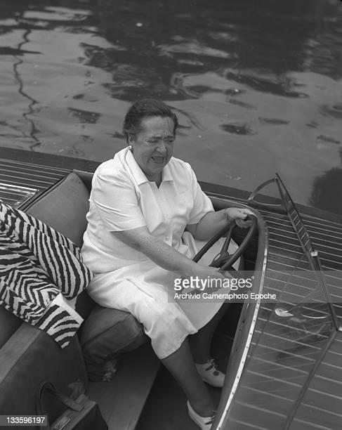 American gossip columnist Elsa Maxwell driving a water taxi Lido Venice 1948