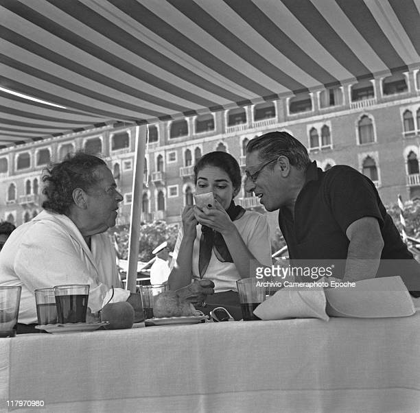 American gossip columnist Elsa Maxwell sitting at a table under a striped marquee with Maria Callas Meneghini making up and Aristotele Onassis at...