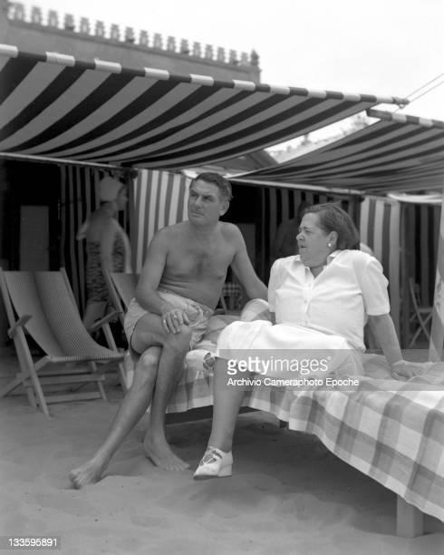 American gossip columnist Elsa Maxwell sitting on the beach with Feldmann Charell, Lido, Venice, 1948.