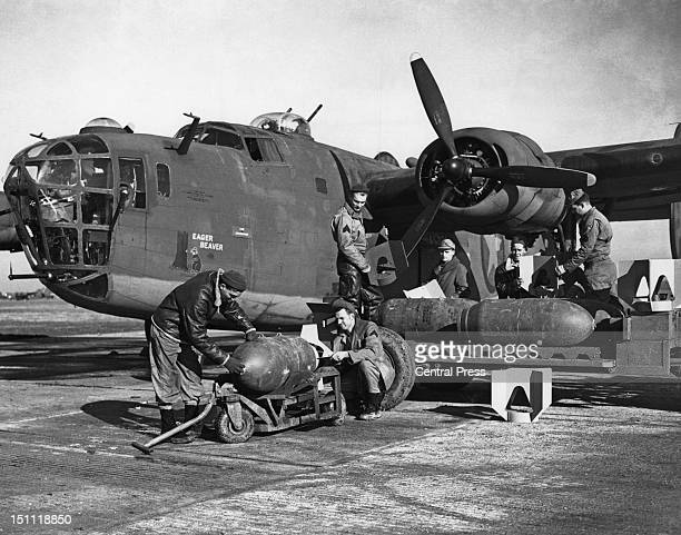 American ground crew priming and loading 1000pound bombs into a B24 Liberator bomber at an Eighth Air Force airfield in England November 1942