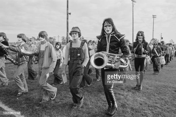 American guitarist Ace Frehley and drummer Peter Criss of rock group Kiss march with members of the Cadillac High School band on the football field...