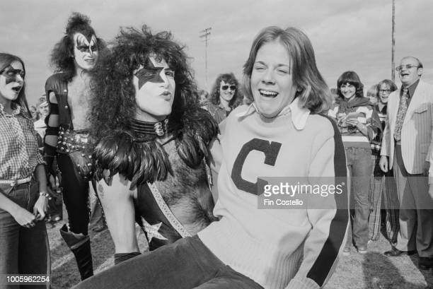 American guitarist and singer Paul Stanley of rock group Kiss holds up a Cadillac High School football fan on the football field during the 'Day in...