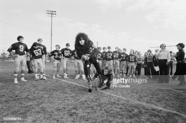 American guitarist and singer Paul Stanley of rock group Kiss is tackled by a member of the Cadillac High School football team on the football field...