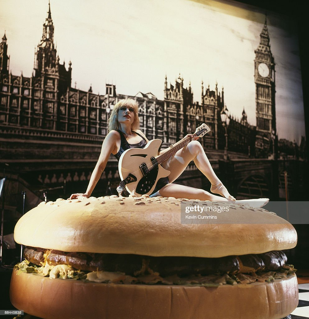 American guitarist Brix Smith, of rock group The Fall, poses on a giant hamburger from the set of the ballet 'I Am Kurious Oranj', performed by Michael Clark and Company, with music by The Fall, at the King's Theatre, Edinburgh, 20th August 1988.