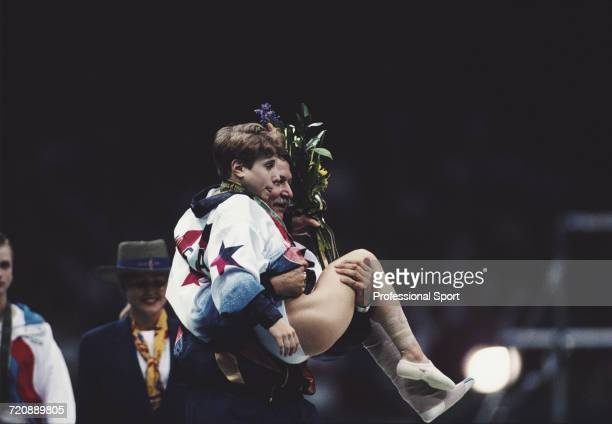 American gymnast Kerri Strug is carried back by coach Bela Karolyi after receiving her gold medal on the medal podium following a foot injury after...