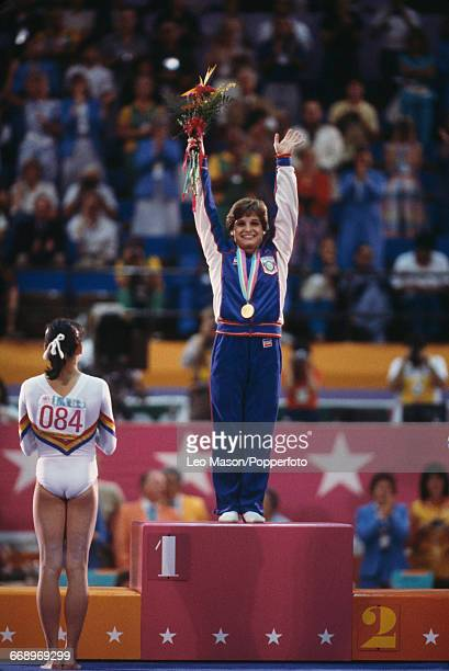 American gymnast Mary Lou Retton stands on the podium and waves to the crowd after finishing in first place to win the gold medal in the Women's...