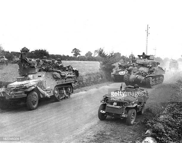 American half-tracks and tanks stir up the dust on a French road as they advance toward Concarneau in Brittany to shell German installations .