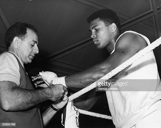 American Heavyweight boxer Cassius Clay has his hands bandaged by manager Angelo Dundee before a bout of sparring at the Royal Artillery gym London...